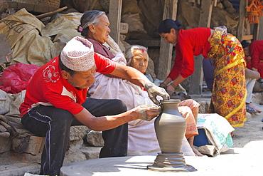 Potter turning pot on wheel, Potter's Square, Bhaktapur, Nepal, Asia