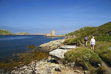 Walkers near Cromwell's Castle in summer sunshine, Isle of Tresco, Isles of Scilly, United Kingdom, Europe