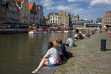 Young people enjoy summer sunshine along the Graslei and Korenlei, Ghent, Belgium, Europe