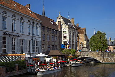 Tourists in boats travel on the Den Dijver canal in summer, Bruges, West Flanders, Belgium, Europe