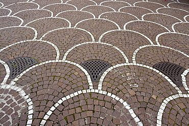 Bicolour cobble fan pattern paving with bespoke manhole covers, EUR district, Rome, Latium, Italy, Europe