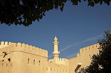 View of the fort of Nizwa, with the minaret of the Sultan Quaboos Mosque, Oman, Middle East