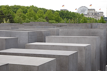 Field of steles, designed by Peter Eisenman, the Memorial to the Murdered Jews of Europe, the Reichstag building at back, Bundestag, Berlin, Germany, Europe
