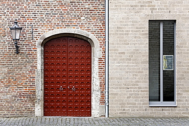 Medieval brick wall with gate side by side with a new wall with modern windows, Stiftsmuseum monastery museum, Xanten, Lower Rhine region, North Rhine-Westphalia, Germany, Europe
