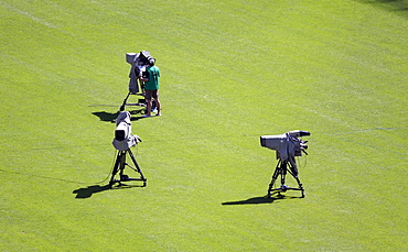 Camera operator standing on the lawn in a stadium at a sporting event