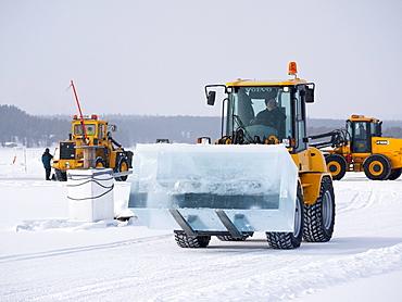 Near the ice hotel in Jukkasjaervi, large blocks of ice are cut and lifted from the frozen Torne Aelv River with heavy equipment, Jukkasjaervi, Kiruna, Lappland, northern Sweden, Sweden, Europe
