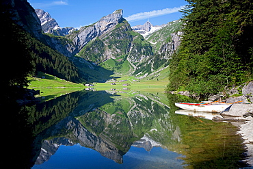 Calm morning view at Lake Seealpsee with reflections, view towards Saentis Mountain and two rowing boats in the foreground, Alpstein range, Appenzell region, Switzerland, Europe