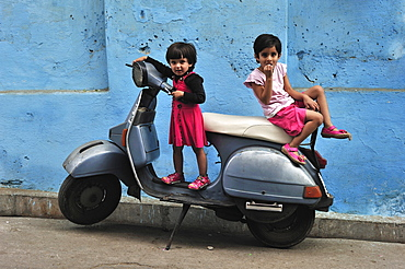Young children playing on a motor scooter, Udaipur, Rajasthan, India, Asia