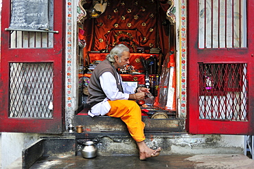 A Brahmin man seated in a small Hindu temple covering a deity with aluminum foil, Udaipur, Rajasthan, India, Asia