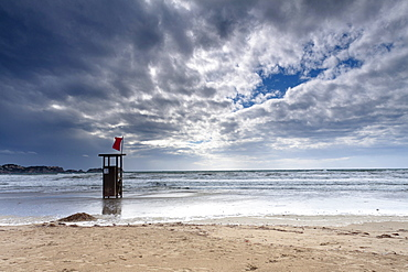 Lifeguard watch tower on the Playa Tora beach with red flag and distinctive clouds, Peguera, Majorca, Balearic Islands, Spain, Europe
