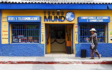 A man with traditional dress passes by a telecommunication shop, Solola Department, Guatemala, Central America