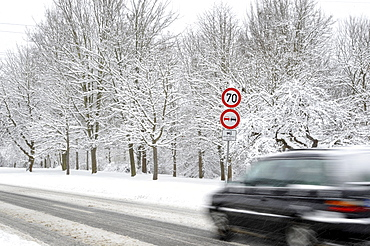 Car on a snow-covered road in winter, slip hazard, warning sign, prohibition sign, blur