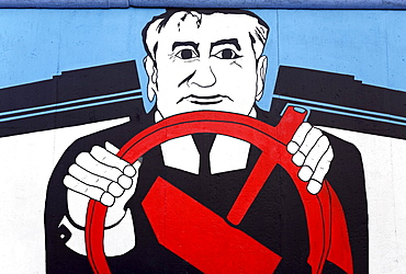 Gorbachev sitting behind a steering wheel made from the Communist hammer symbol, painting on the remants of the Berlin Wall, Friedrichshain district, Berlin, Germany, Europe