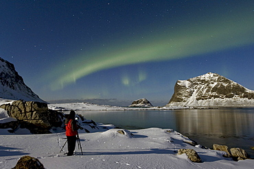Photographer taking pictures of Polar lights (Aurora borealis), in the Vikbukta bay, Vestvagoya, Lofoten, Norway, Europe