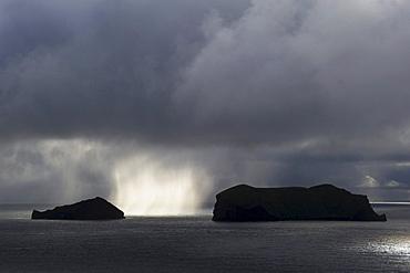 Sunlit rain between two Westman Islands or Vestmannaeyjar, South Iceland, Europe