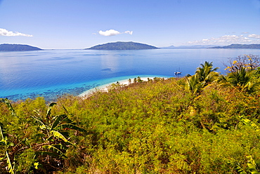 The crystal clear waters and white sand beach of Nosy Tanikely, in the distance, Nosy Komba, Nosy Be, Madagascar, Africa