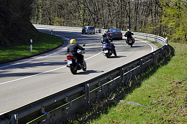 Motorcyclists in a curve on a country road with guard rail for protection, Eifel, Germany, Europe