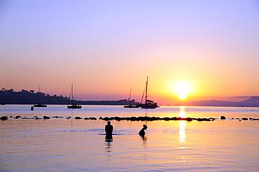 People bathing at sunrise, boats in the Bay of Puerto de Pollensa, Port de Pollenca, Majorca, Balearic Islands, Mediterranean Sea, Spain, Europe
