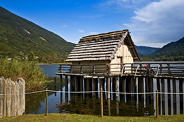 Replica of wooden house with thatched roof on stilts, lake Revine, Cansiglio plateau, Treviso, Veneto, Italy, Europe