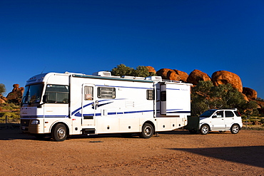 Campervan with a car attached to the back, parked on a campsite, Devils Marbles, Northern Territory, Australia