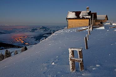 Evening mood on the wintery Hochalp mountain pasture, with the Urnaesch village, Swiss Alps, Alpstein range with Mt. Saentis, Switzerland, Europe