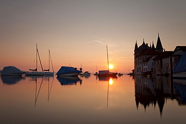 Turmhof building in Steckborn on Lake Constance at sunrise with boats on buoys and reflections in the water, Switzerland, Europe