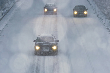 Three cars driving in a snow flulrry on a highway