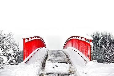 Red pedestrian bridge in the snow