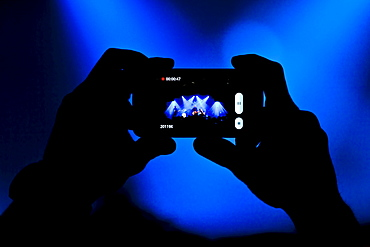 Concert-goer taking a picture with an iPhone