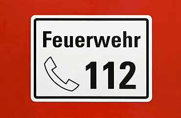 """Sign, """"Feuerwehr 112"""", German for """"fire service 112"""", emergency telephone number, on a red surface"""
