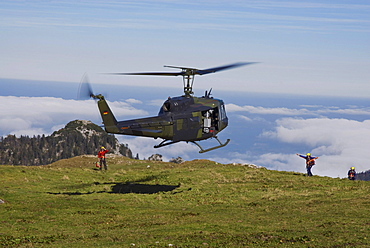 Landing Bundeswehr military helicopter marshalled by rescue personnel, Bavarian Alps, Upper Bavaria, Bavaria, Germany, Europe