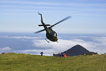 Helicopter being marshalled by rescue workers, German army helicopter in approach for landing, Chiemgau Alps, Bavaria, Germany, Europe