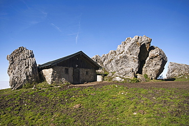 Stone house on Steinlingalm alp, built next to large limestone rocks, Kampenwand mountain massif, Chiemgau, Kampenwand mountain, Upper Bavaria, Germany, Europe
