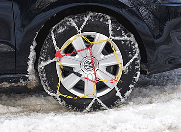 Car tyre with mounted snow chains in the snow