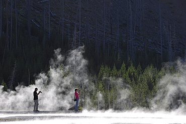 Tourists taking photos while on a boardwalk amidst the steam of the springs and geysers, Black Sand Basin, Upper Geyser Basin, Yellowstone National Park, Wyoming, United States of America, USA