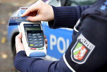 Police officer with BARVUS device for cashless payment of caution money, fines, tickets with credit card