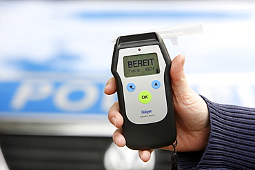 Police officer with breathalyser for checking the fitness to drive