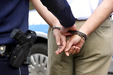 Man in a suit is led off in handcuffs by a police officer