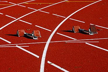 Tartan track of a sports field, starting blocks for sprinting disciplines, lane markings