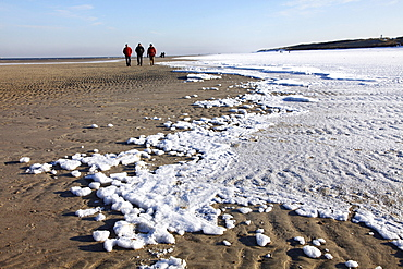 People walking along the snow-covered beach on the East Frisian North Sea island of Spiekeroog, Lower Saxony, Germany, Europe