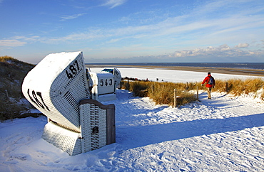 Winter, snow-covered beach with roofed wicker beach chairs, East Frisian North Sea island of Spiekeroog, Lower Saxony, Germany, Europe