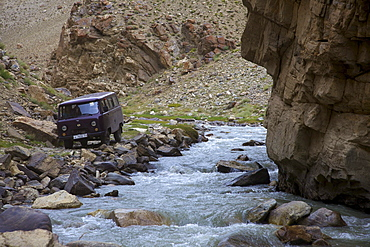 UAZ off-road vehicle bus at a creek in the Pamir mountain range, Tajikistan, Central Asia