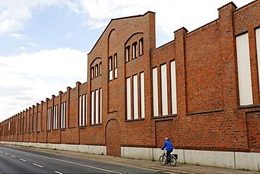 Cyclist riding past the brick facade of a former factory, Batteriestrasse, industrial port of Neuss, Niederrhein, North Rhine-Westphalia, Germany, Europe