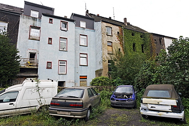 Car wrecks in a backyard, Bruckhausen district, Duisburg, North Rhine-Westphalia, Germany, Europe