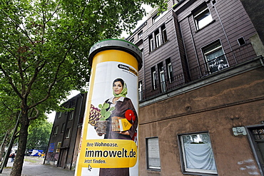 Muslim woman with a headscarf as a promotional figure on a advertising pillar, Bruckhausen district, Duisburg, North Rhine-Westphalia, Germany, Europe
