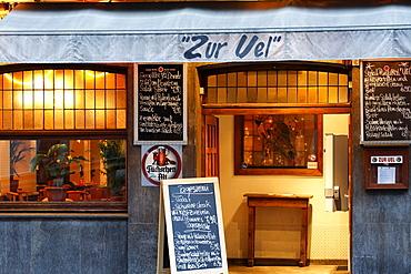 Typical Duesseldorf pub in the historic district, menu board displayed in front of the door, evening mood, Ratinger Strasse street, Duesseldorf, North Rhine-Westphalia, Germany, Europe