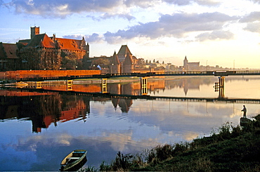 Morning mood with an angler on the Nogat River with Malbork Castle, formerly Marienburg Castle, the seat of the Grand Master of the Teutonic Knights, Malbork, Mazury, Poland, Europe