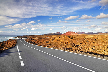 Road on the west coast, in the back the Montanas del Fuego mountains, Lanzarote, Canary Islands, Spain, Europe