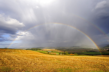 View over a stubble field with rainbow, Hegau region, Landkreis Konstanz county, Baden-Wuerttemberg, Germany, Europe