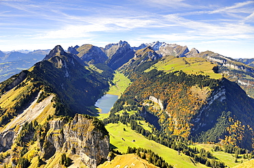 View from Mt. Hoher Kasten over the Stauberenfirst, down to Lake Saemtisersee, on the right Mt. Alp Sigel with the autumnal Sigelwald forest, Mt. Saentis on the horizon, Canton Appenzell Inner-Rhodes, Switzerland, Europe